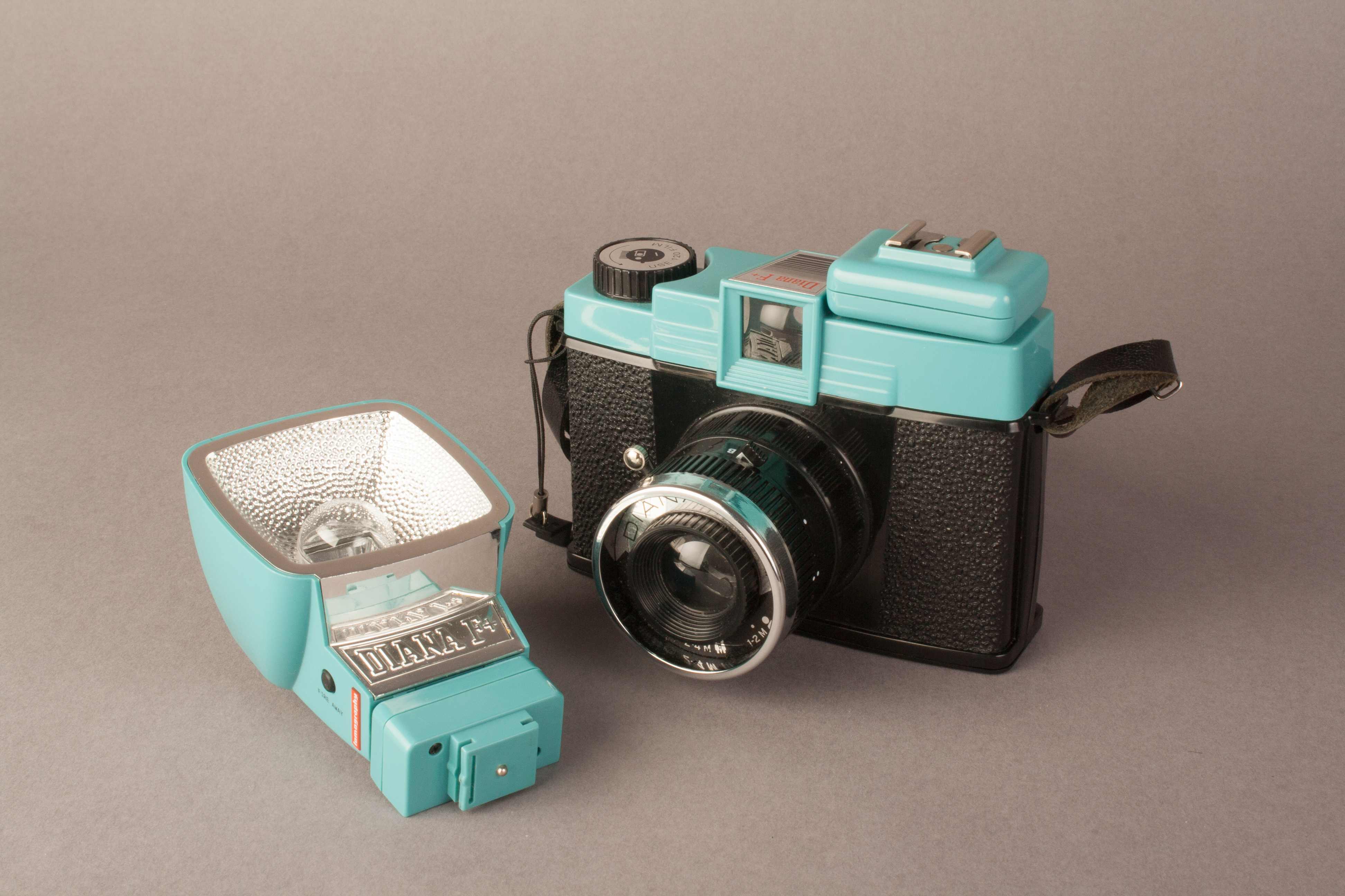 A picture showing the diana F+ with the hot shoe adapter, next to the flash with its own hot shoe adapter